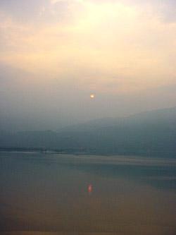 Der Gardasee liegt im Morgengrauen. es ist neblig, die Berge am anderen Ufer sind nur schemenhaft zu erkennen. Doch die Sonne bahnt sich gerade ihren WEg durch den Dunst, ein fahler Punkt und eine orange Spur auf dem Wasser. Bald ist es Tag.