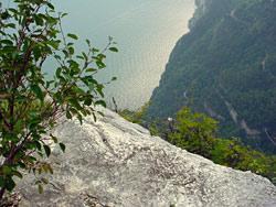 Eine Felsplatte hunderte Meter über dem Gardasee. Man sieht das Ufer.