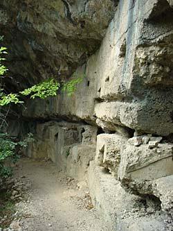 eine brüchige Betonwand mit Schießscharten unter einem Felsüberhang in den Bergen um den Gardasee.