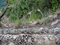 Ein mit Maschendraht vor Steinschlag geschützter senkrechter Abhang. Blick von oben.