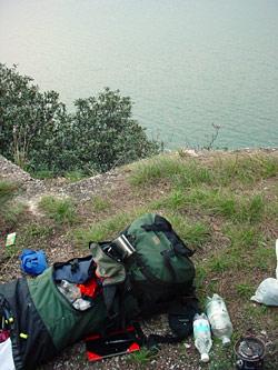 Ein Wanderrucksack liegt halb ausgepackt auf einem Plateau über dem Gardasee. Daneben ein Campingkocher, mehrere Wasserflaschen und ein Notizbuch.
