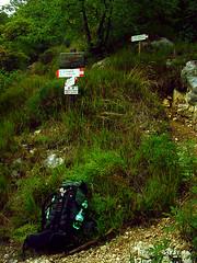 Wanderweg 404 am Gardasee. eine Weggabelung und ein abgestellter Wanderrucksack.
